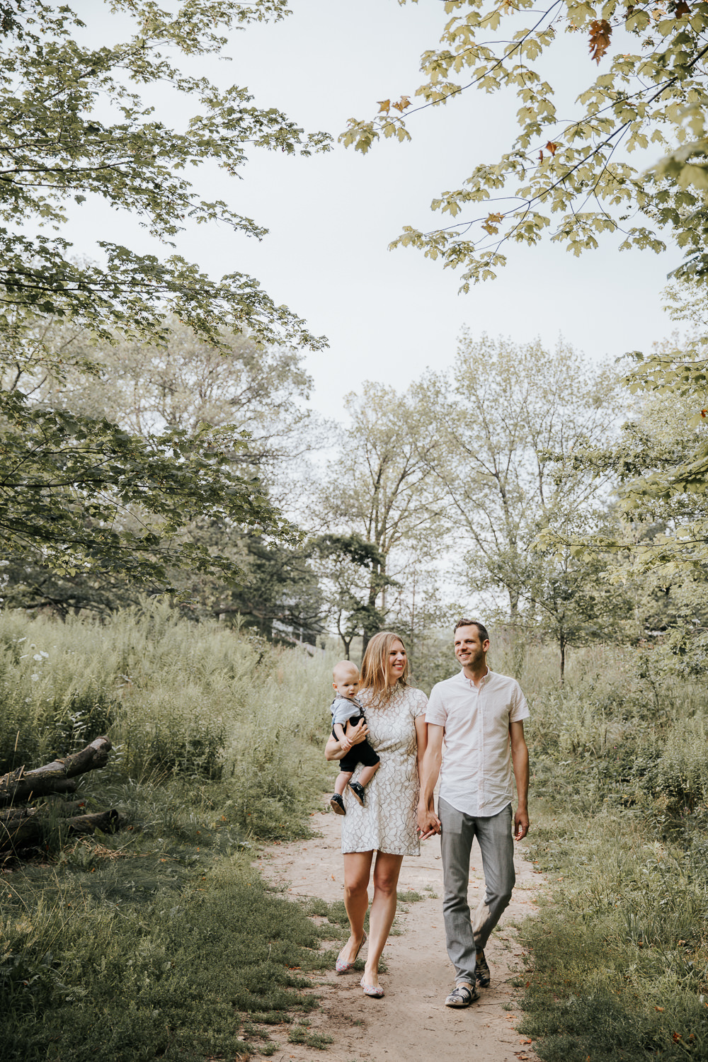 family of 3 walking down dirt path at high park surrounded by tall grasses and trees, mom carrying 8 month old blonde baby boy and parents holding hands, wife smiling at husband - York Region In-Home Photography