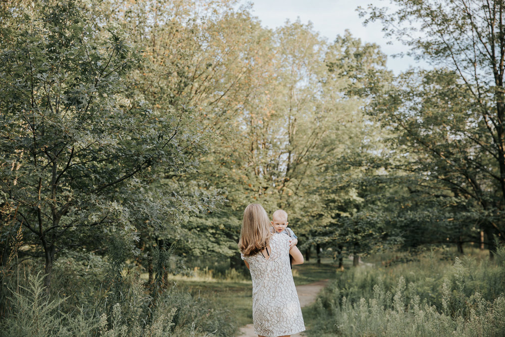mother carrying 7 month old blonde baby boy down path at high park surrounded by greenery, son peeking over mom's shoulder -Stouffville In-Home Photos