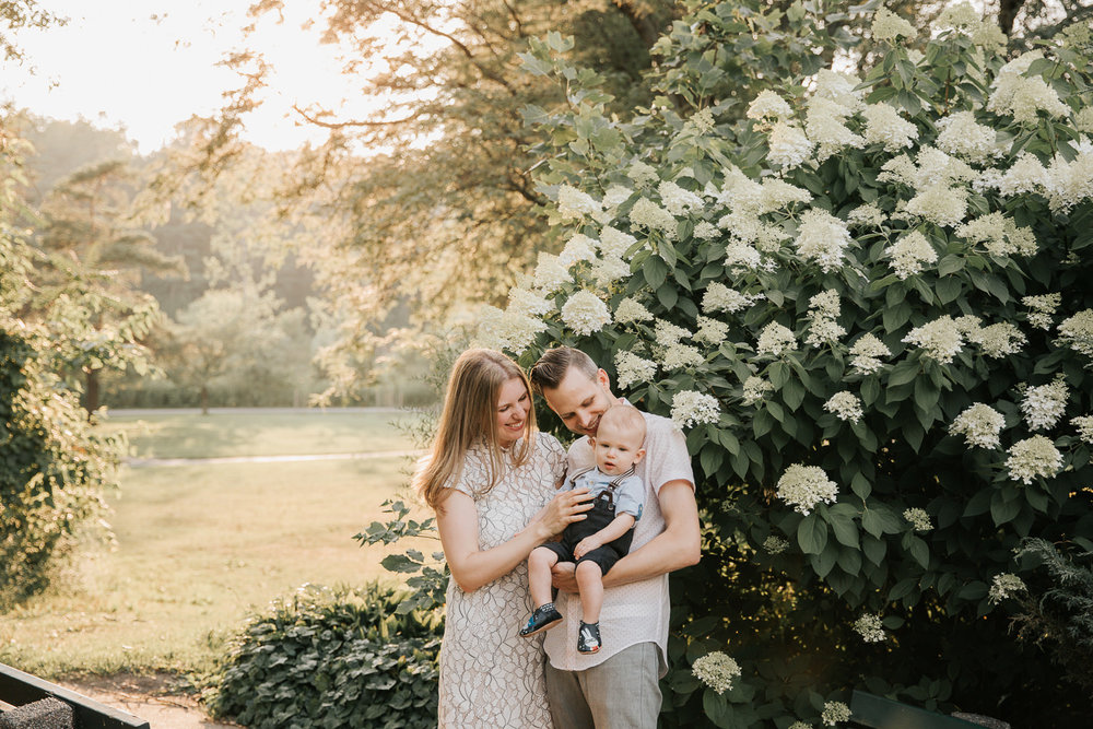 family of 3 standing in high park, setting golden sun behind them, father carrying 8 month old blonde baby boy and mom resting hand on baby, parents smiling at son - York Region In-Home Photos