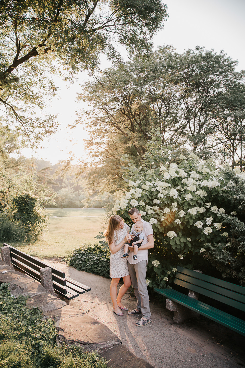 family of 3 standing in high park, setting golden sun behind them, father carrying 8 month old blonde baby boy and mom resting hand on baby, parents smiling at son -Stouffville Lifestyle Photos