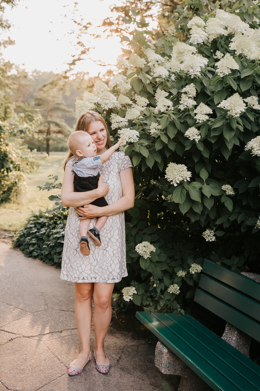 mom standing next to bench in garden at high park with 8 month old blonde baby boy in her arms, son reaching for flower on bush and mother smiling -Barrie Lifestyle Photos
