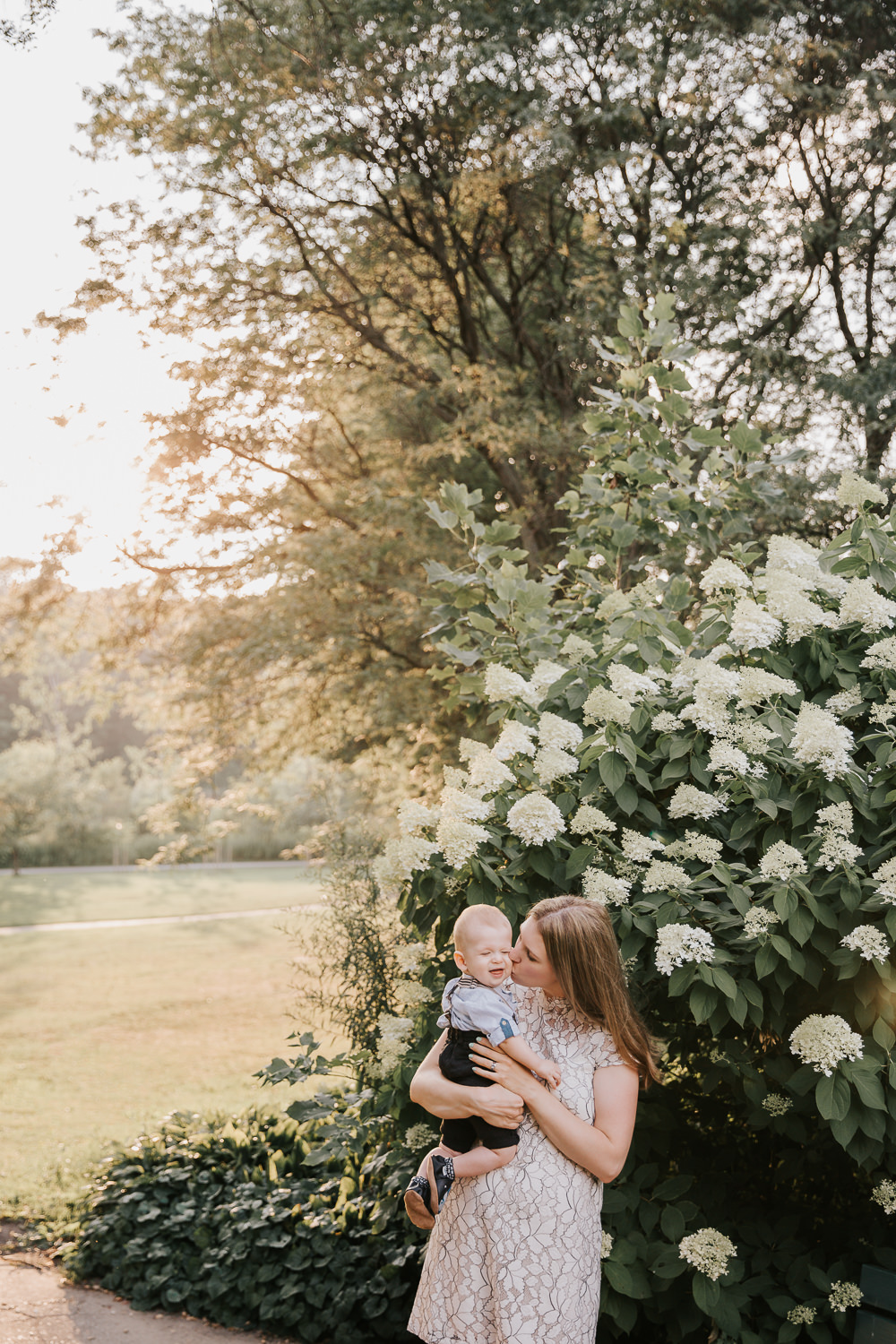 mom standing in garden at high park with 8 month old blonde baby boy in her arms kissing son on the cheek as he smiles -GTA Lifestyle Photos
