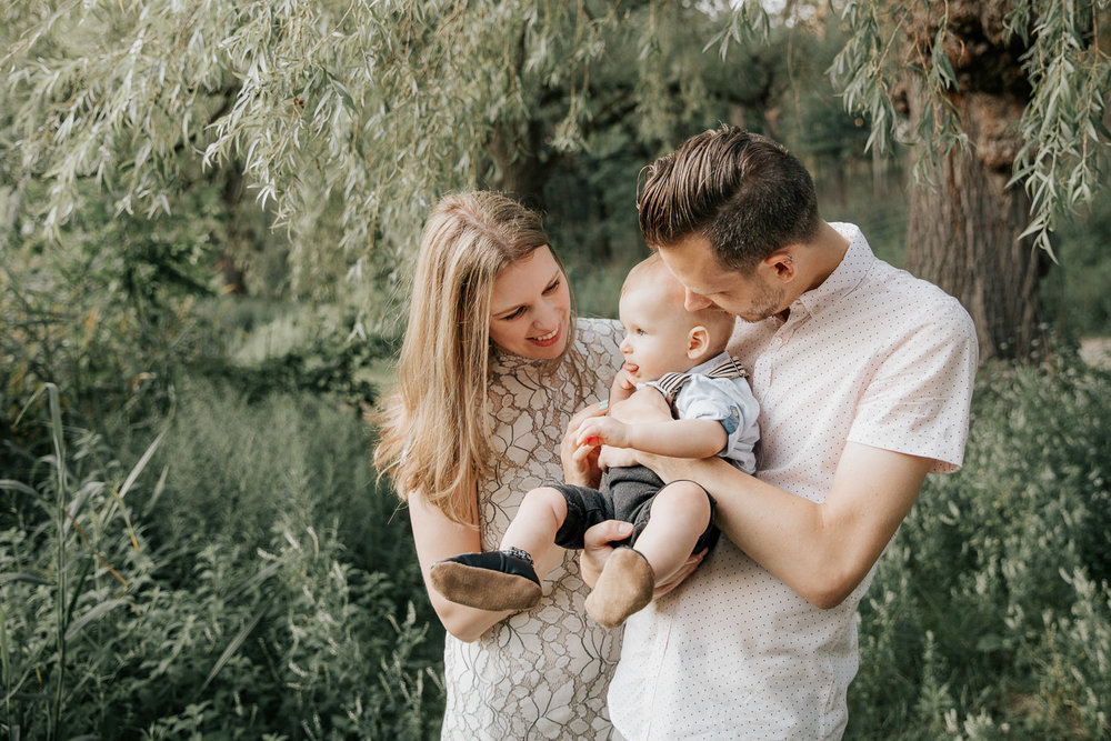 family of 3 standing under willow tree next to pond at high park, father carrying 8 month old blonde baby boy and mom holding his hand, parents smiling at son -York Region LifestylePhotos