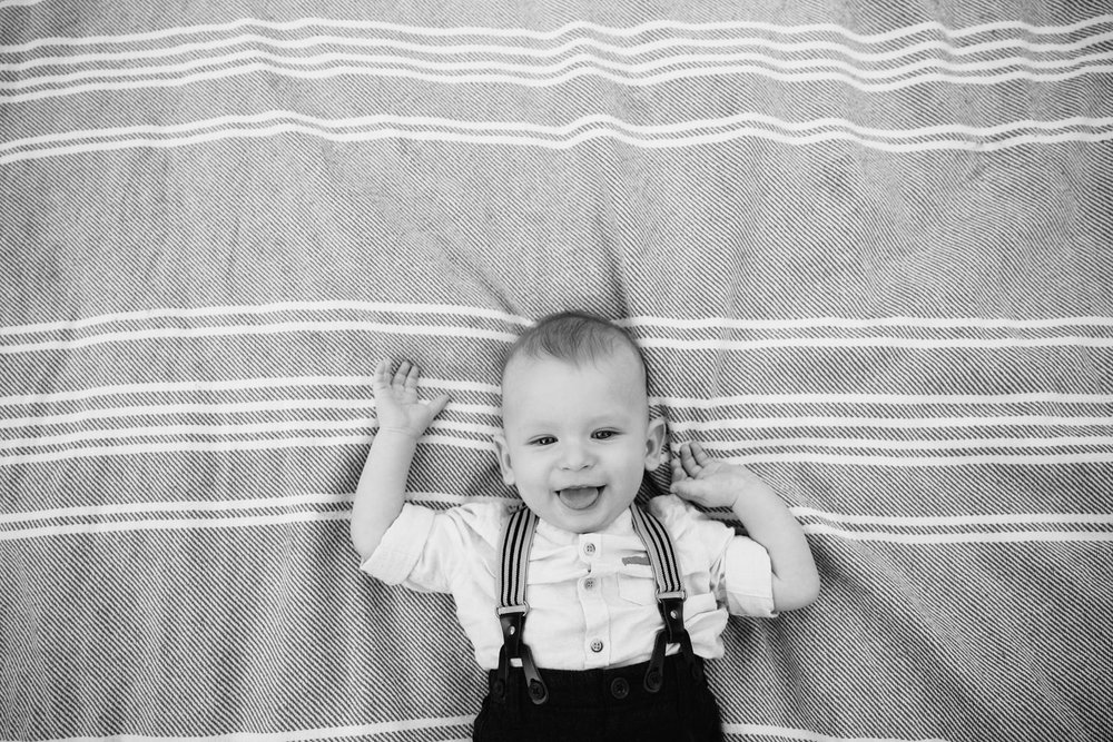 8 month old baby boy lying on grey and white striped blanket, arms in the air and smiling at the camera - Barrie Lifestyle Photography