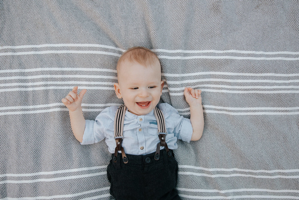 8 month old baby boy lying on grey and white striped blanket, arms in the air and laughing showing two bottom teeth - GTA LifestylePhotography