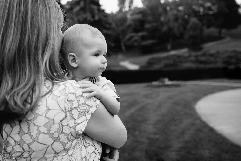 8 month old baby boy in mom's arms, hand on her shoulder looking tired off into the distance - York Region Lifestyle Photography