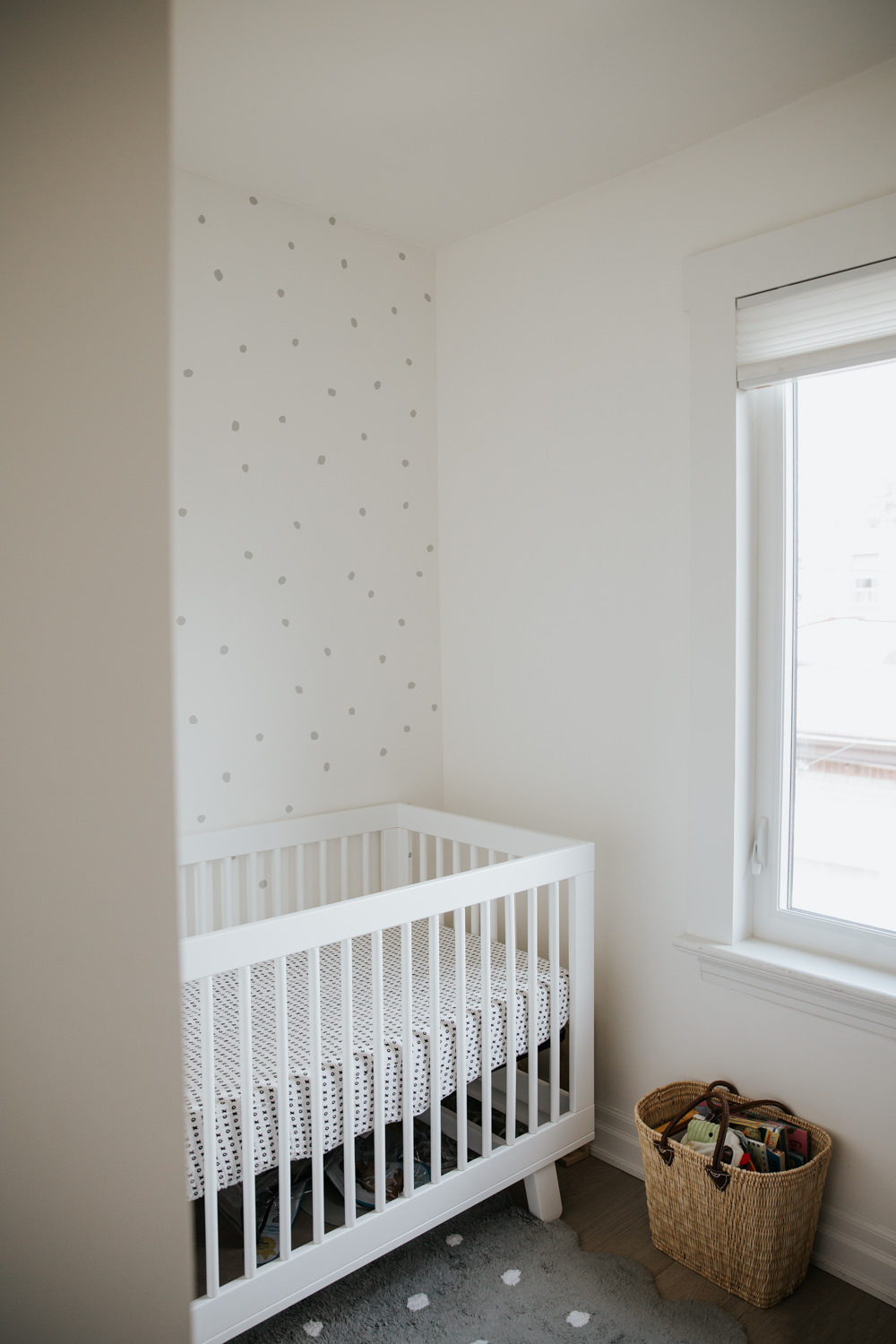 neutral nursery, white crib, grey polka dots on wall behind, natural wicker basket under window -Barrie Lifestyle Photography