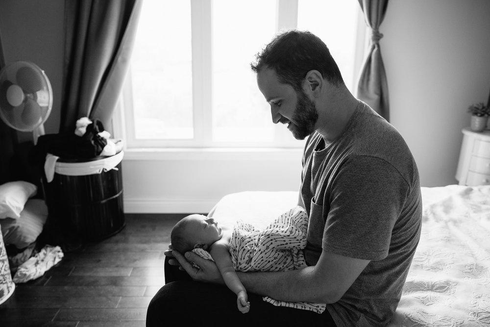 new dad in grey t-shirt sitting on edge of master bed holding sleeping 2 week old baby girl with light hair wrapped in swaddle - York Region In-Home Photos