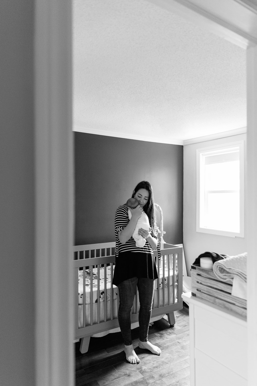 new mom standing in nursery in front of crib holding 2 week old sleeping baby girl wrapped in white swaddle to her chest, mother's eyes closed - Stouffville Lifestyle Photos