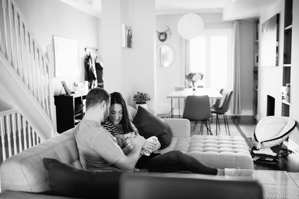 family of 3, new parents cuddle on couch, mom holding 2 week old baby girl covered with black and white swaddle, dad embracing wife and daughter - York Region Lifestyle Photos