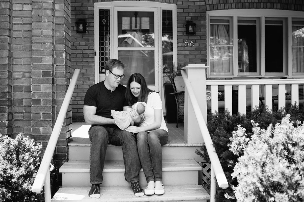 family of 3 sitting on front porch on summer day, dad holding 2 week old baby girl, mom leaning in next to husband smiling at daughter - Barrie Lifestyle Photography
