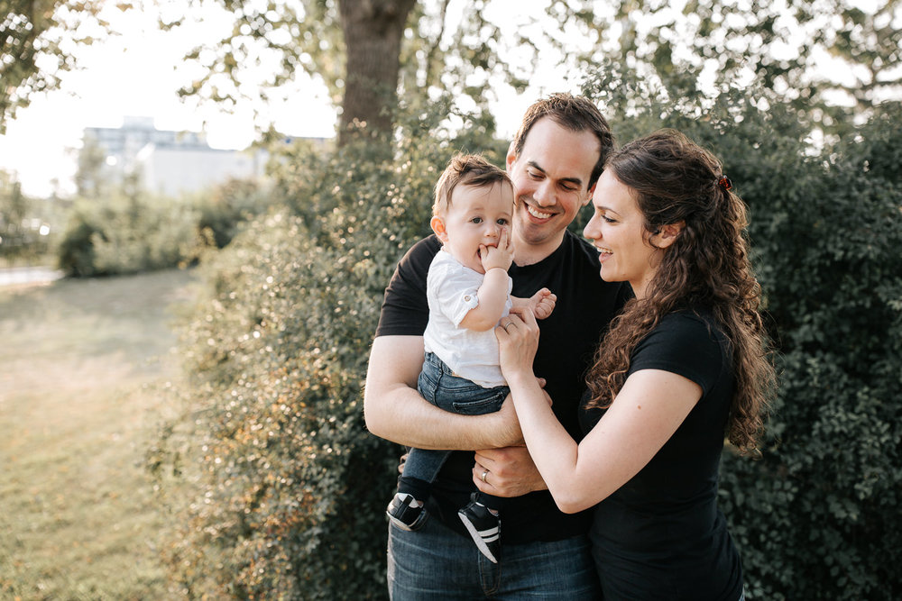 family of 3, smiling parents standing in park holding 9 month old baby boy with brown hair, chewing on hand - Newmarket Lifestyle Photography