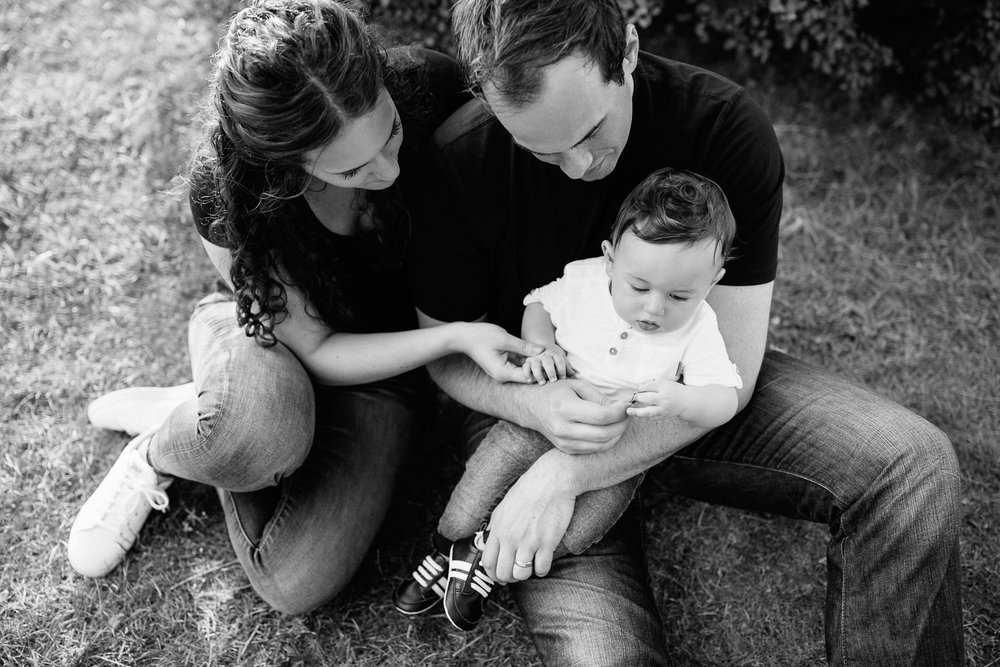 family of 3 sitting on ground in park, 9 month old baby boy with dark hair sitting in dad's lap, mom snuggled next to them holding son's hand - York Region Lifestyle Photography