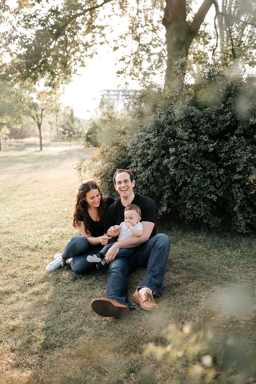 family of 3 sitting on ground in park, 9 month old baby boy with dark hair sitting in dad's lap chewing on hand, mom snuggled next to them, father laughing -Newmarket Lifestyle Photos