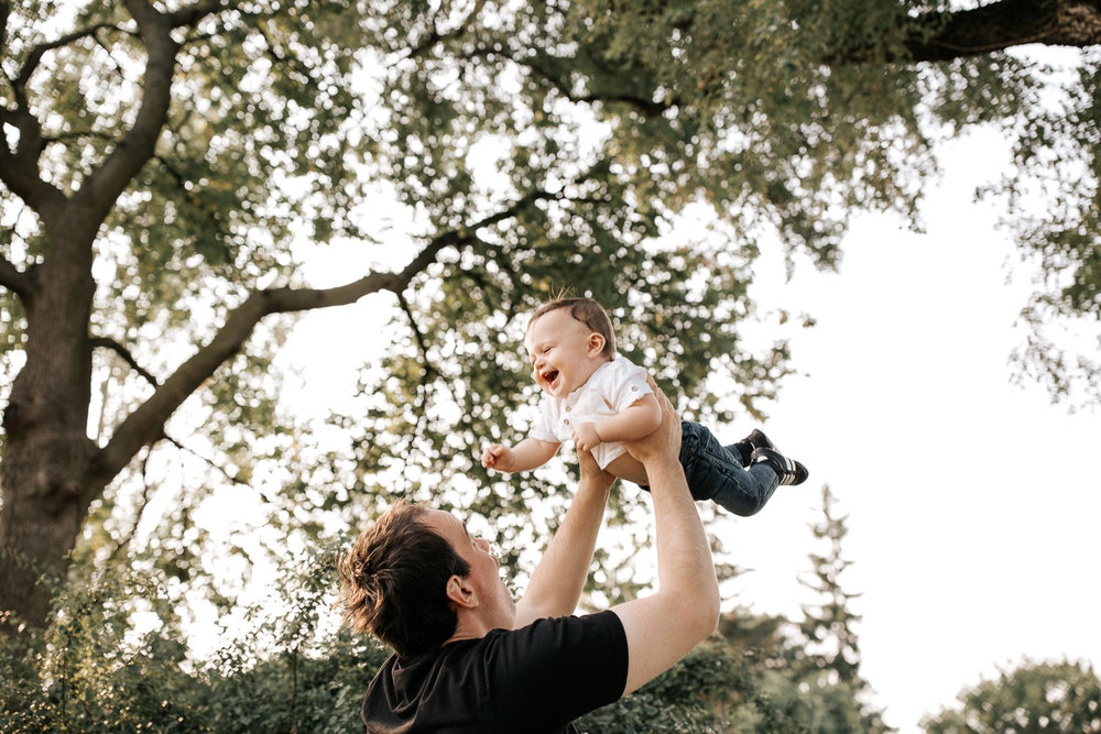 9 month old baby boy with dark brown hair wearing white t-shirt and jeans laughing as dad throws him in air under trees in park - Stouffville Lifestyle Photos