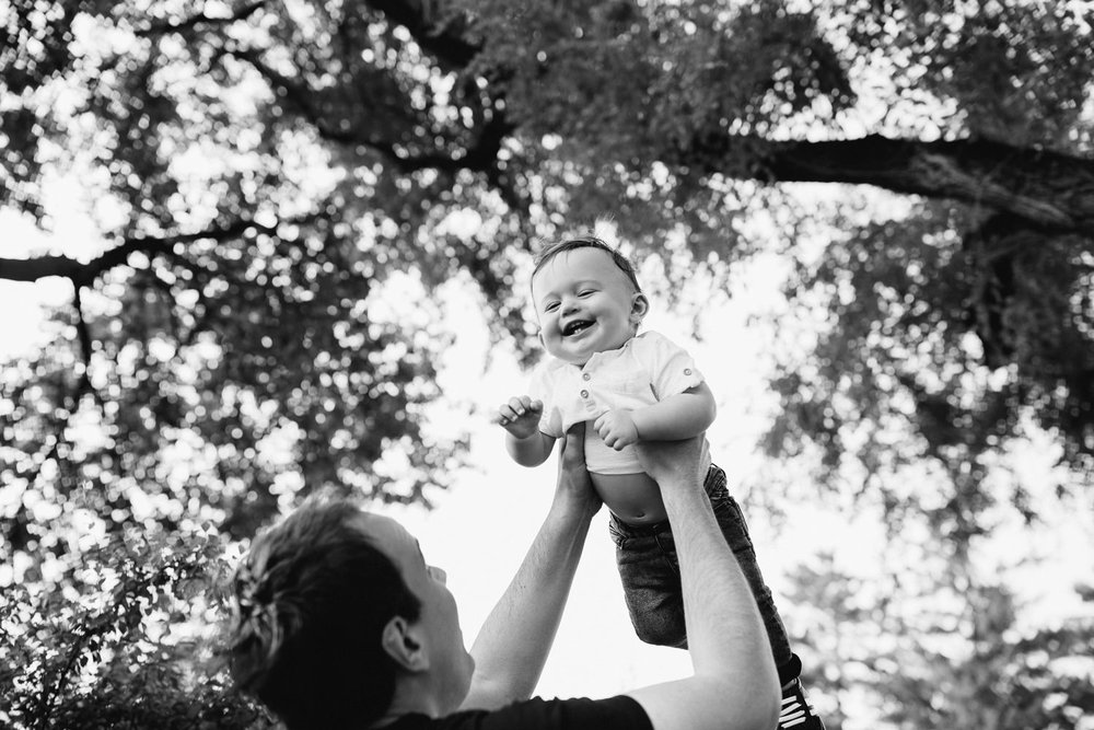 9 month old baby boy with dark brown hair wearing white t-shirt and jeans laughing as dad throws him in air under trees in park - Barrie Lifestyle Photos