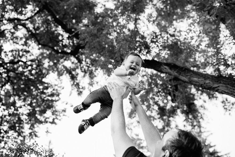 9 month old baby boy with dark brown hair wearing white t-shirt and jeans laughing as dad throws him in air under trees in park - York Region Lifestyle Photos