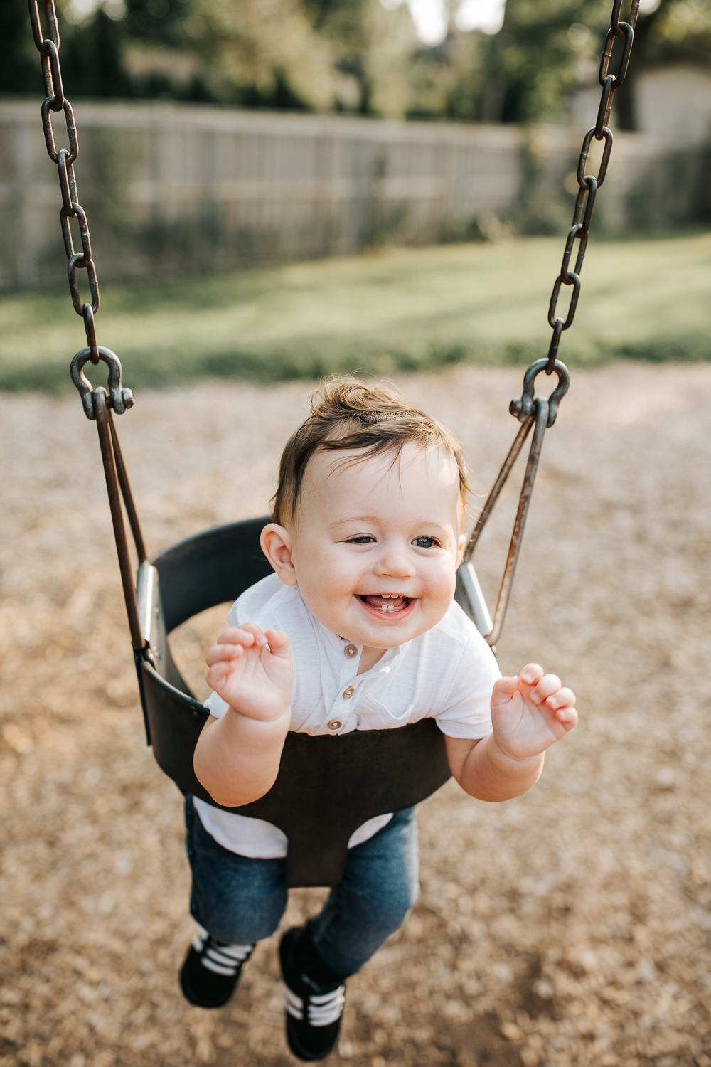 9 month old baby boy with dark brown hair wearing white t-shirt and jeans smiling and laughing with hands in air as he sits in swing at park -Markham Golden Hour Photography