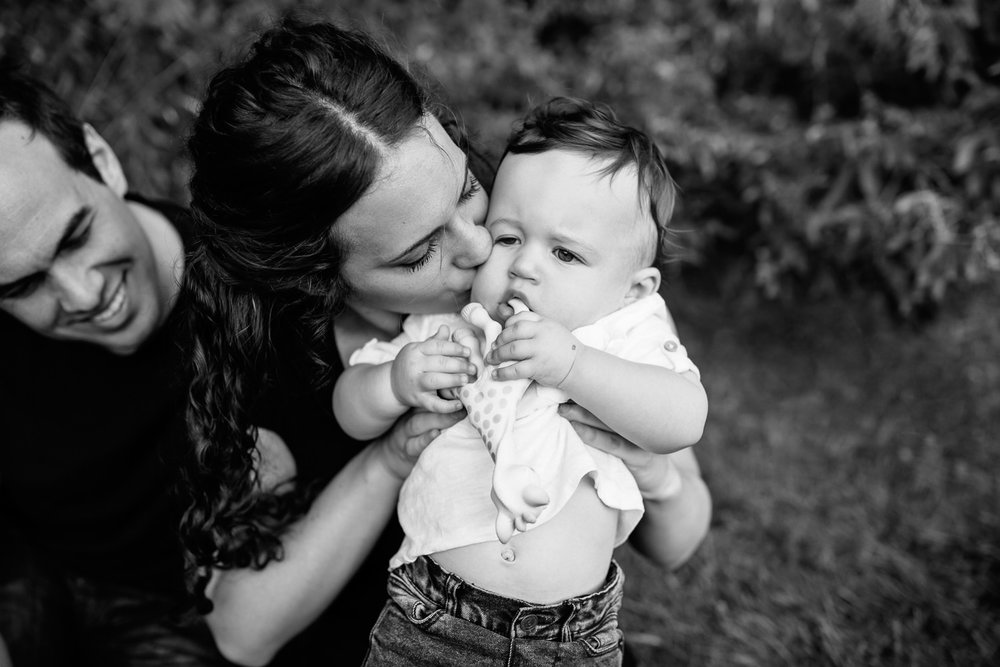 mom holding up 9 month old baby boy with dark hair chewing on Sophie the giraffe, mother kissing son on cheek, dad sitting behind smiling - Stouffville Lifestyle Photography