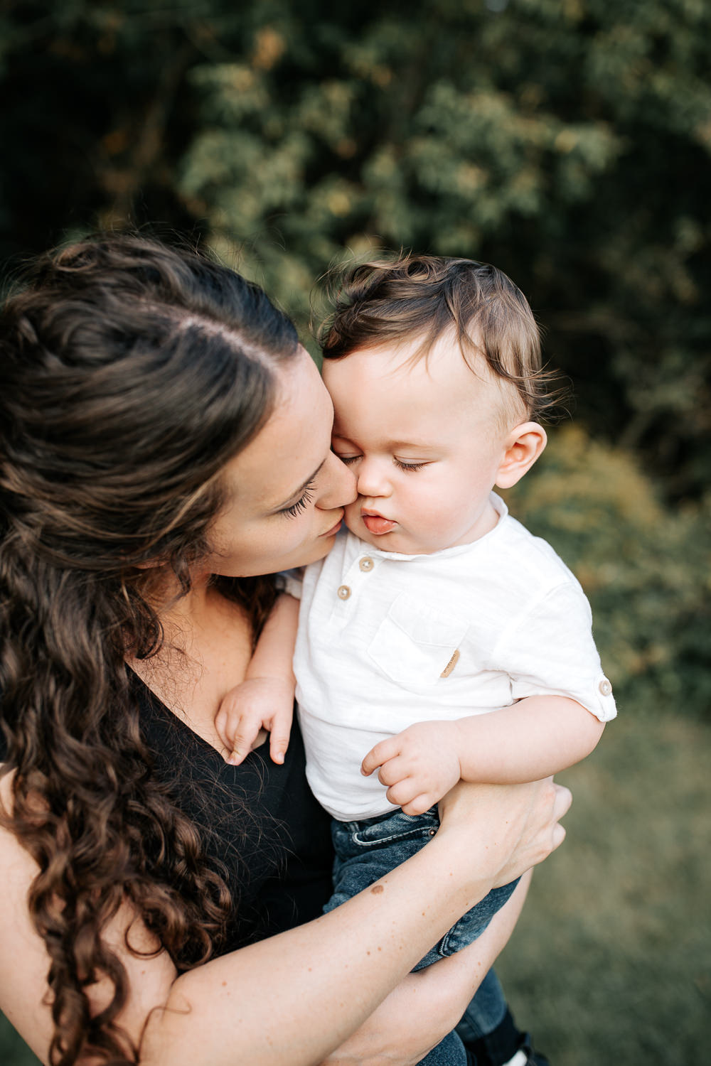 mom standing holding 9 month old baby boy with dark hair wearing white t-shirt and jeans, kissing son on cheek -Barrie Lifestyle Photography