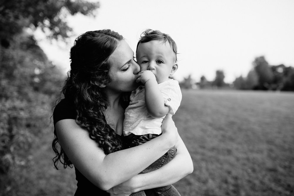 mom standing holding 9 month old baby boy with dark hair wearing white t-shirt and jeans, kissing son on cheek, boy looking at camera -GTA Lifestyle Photography