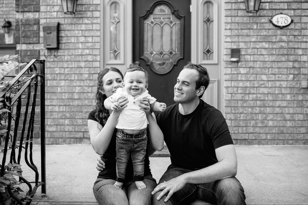 family of 3 sitting on front steps of home, mom holding 9 month old baby boy with dark hair who is standing in her lap, dad sitting next to wife and son smiling - GTA Lifestyle Photos
