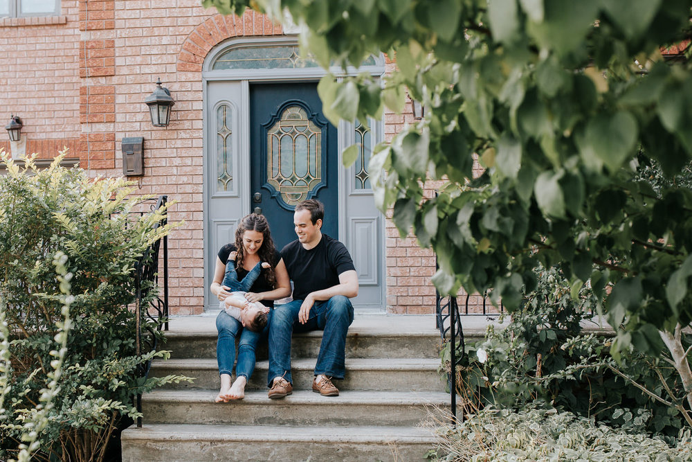 family of 3 sitting on front steps of home, mom tickling 9 month old baby boy with dark hair who is lying in her lap, dad sitting next to wife and son smiling - Barrie Lifestyle Photos