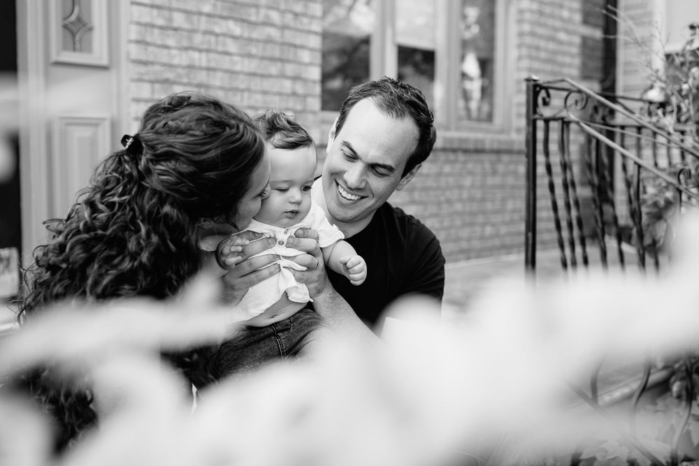 family of 3 sitting on front porch, 9 month old baby boy with dark hair in white t-shirt and jeans standing in dad's lap, mom kissing son on cheek - York Newmarket Golden Hour Photos