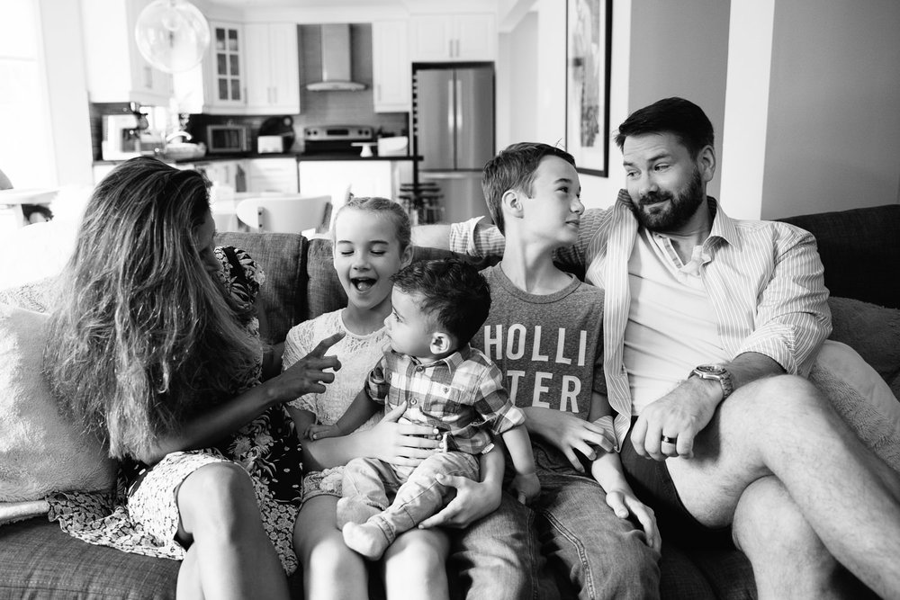 family of 5 sitting on grey couch smiling at one another, 1 year old baby boy sitting in older sister's lap, next to brother, parents on each side - Barrie Lifestyle Photography