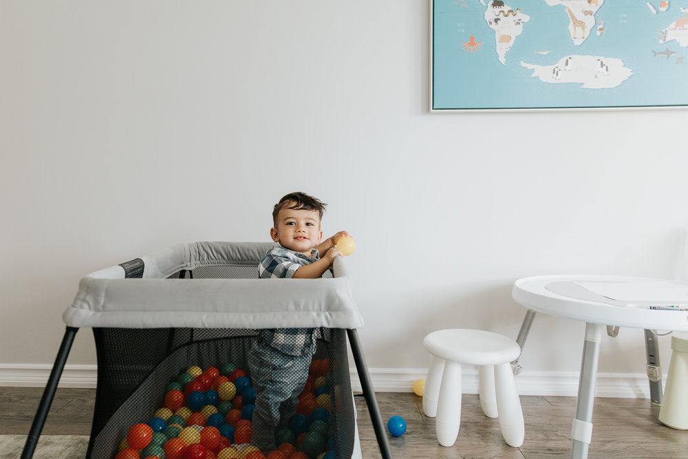 1 year old baby boy with dark hair and eyes in plaid blue and white button down shirt standing in playpen full of plastic balls smiling at camera - GTA In-Home Photography