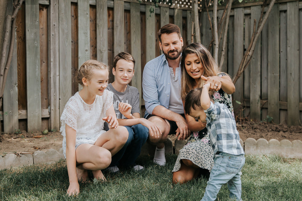 family of 5 in backyard sitting on grass smiling as mom hold 1 year old baby boy's hand while he tries to walk, dad, brother and sister smiling - Stouffville Lifestyle Photos
