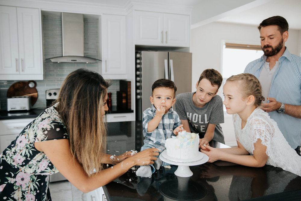 family of 5 standing around island in kitchen watching 1 year old baby boy doing first birthday cake smash - Markham In-Home Photos