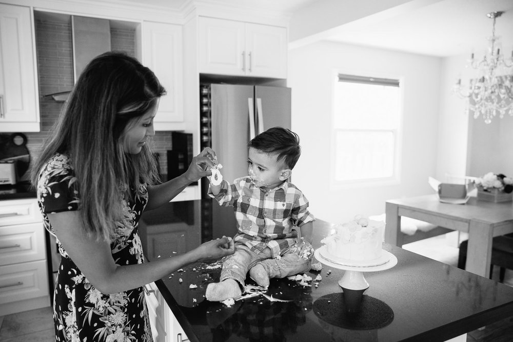 1 year old baby boy with dark brown hair and eyes in blue and white plaid shirt sitting on kitchen counter doing cake smash and playing with icing with mom - Stouffville In-Home Photography