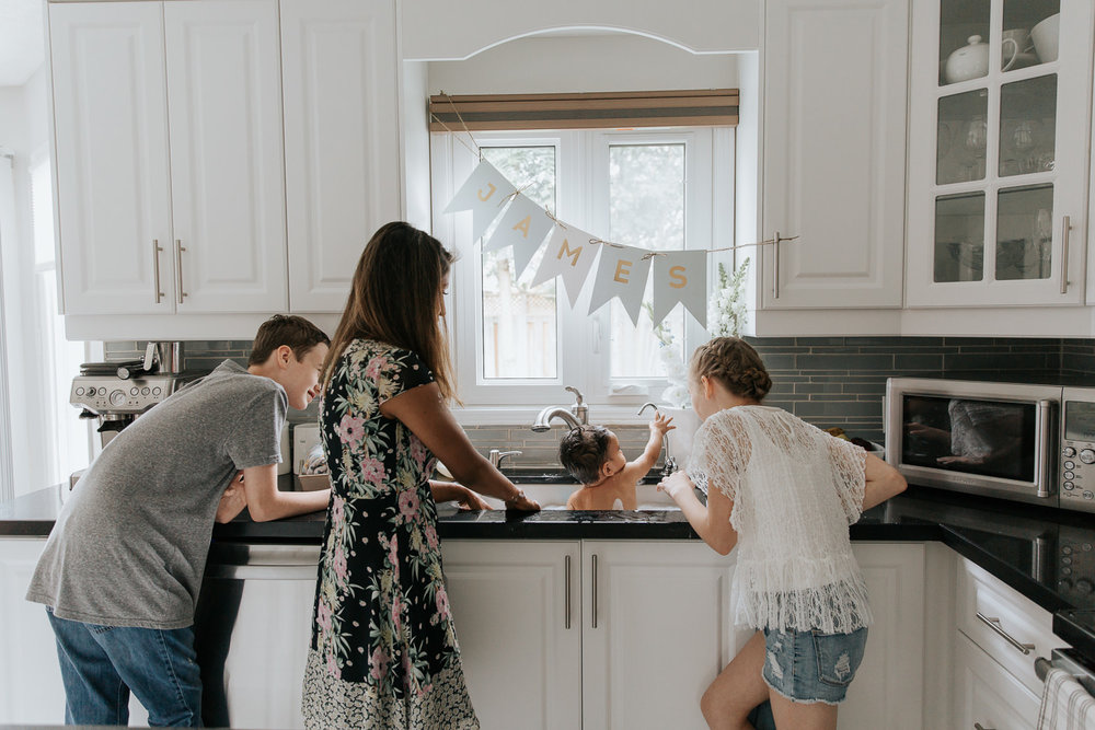 mom, 11 year old girl and 13 year old boy standing at kitchen sink giving 1 year old baby brother a bath - York Region Lifestyle Photography