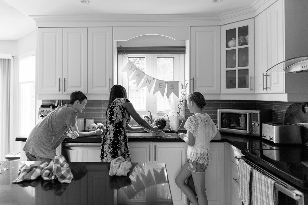 mom, 11 year old girl and 13 year old boy standing at kitchen sink giving 1 year old baby brother a bath - Newmarket Lifestyle Photos
