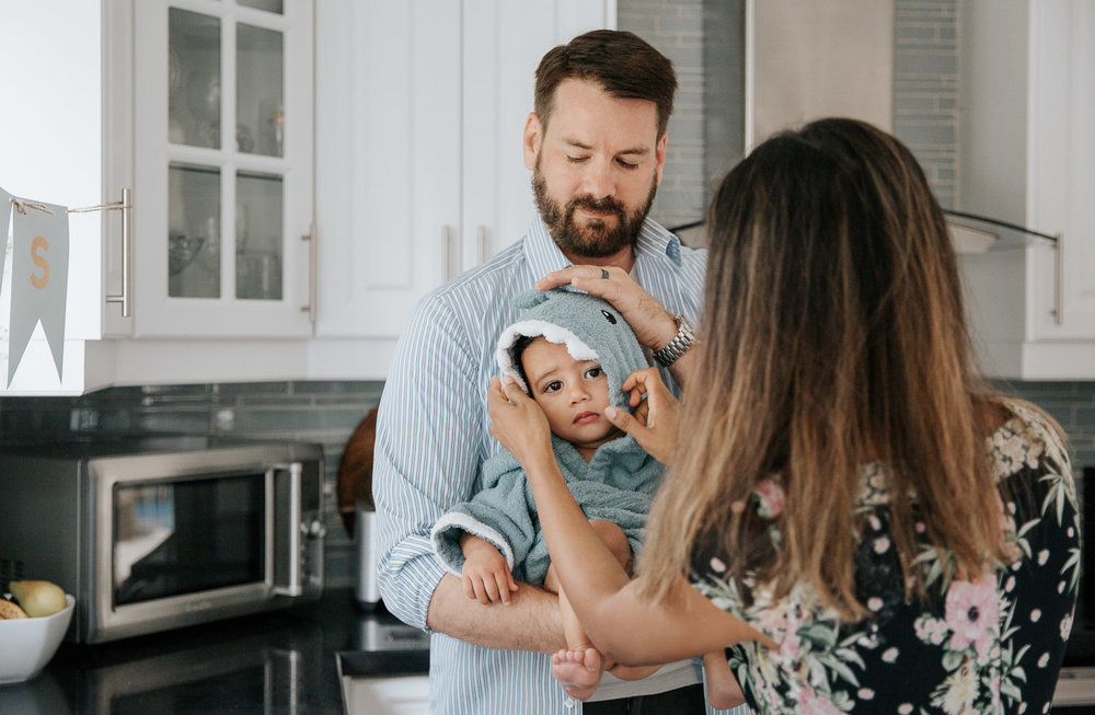 dad standing in kitchen holding 1 year old baby boy fresh out of bath, mom wrapping son in blue shark hooded towel - GTA Lifestyle Photos