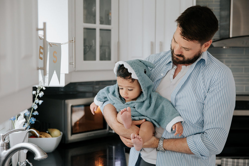 dad standing in kitchen holding 1 year old baby boy fresh out of bath, son wrapped in blue shark hooded towel - York Region Lifestyle Photos