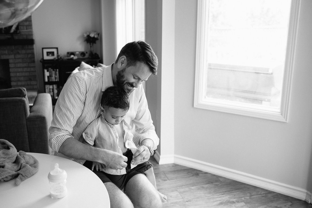 1 year old baby boy with dark hair and long eyelashes sitting in dad's lap as father button's son's shirt - GTA In-Home Photos