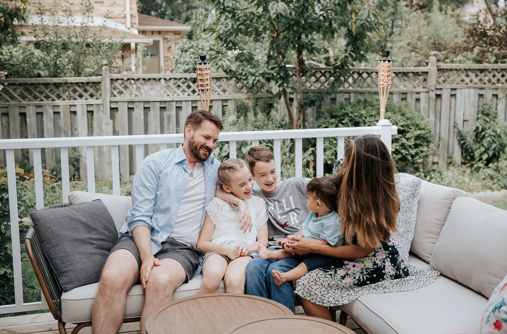 family of 5 sitting on couch on backyard deck, 11 year old girl, 13 year old boy and 1 year old baby sitting between parents, everyone looking at each other laughing - Barrie Lifestyle Photography
