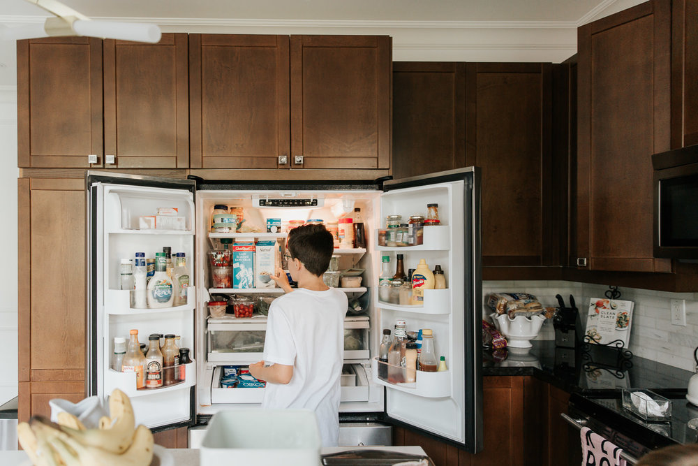 13 year old boy standing in front of open fridge looking for milk as he helps prepare family brunch - Markham Lifestyle Photos