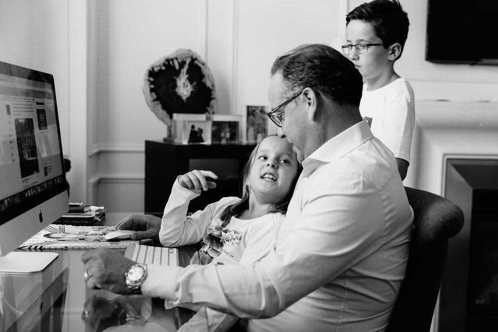 8 year old girl sitting in dad's lap as they sit at his desk, daughter looking up and talking to father, older brother standing behind them - York Region Lifestyle Photography