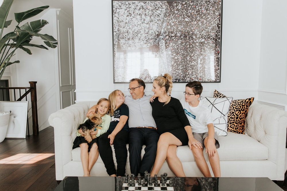 family of 5 sitting on couch together, smiling at one another, 2 daughters 1 son, 8 year old girl holding yorkie dog in lap - York Region In-Home Photography