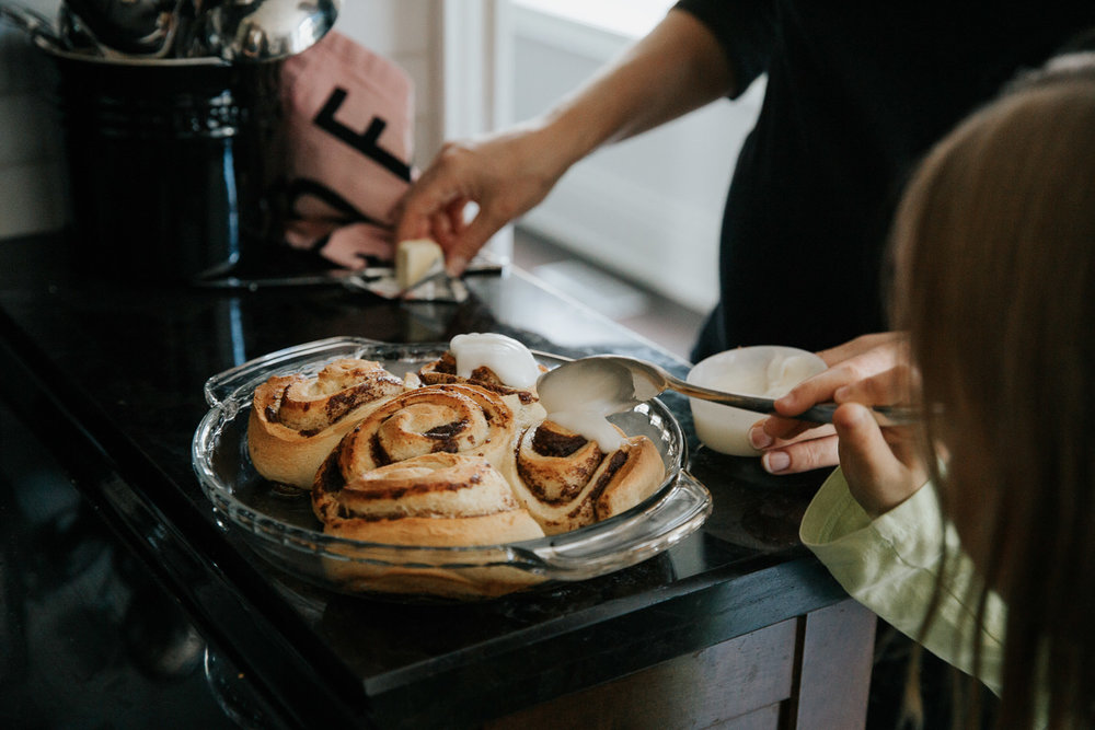 8 year old girl putting icing on cooked cinnamon buns for family brunch with help from mom - GTA In-Home Photos