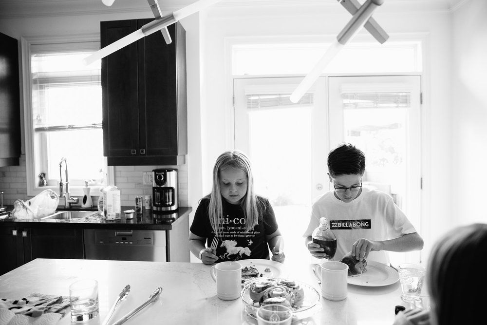 10 year old girl and 13 year old boy sitting next to one another at kitchen island eating brunch with their family - Stouffville Lifestyle Photos