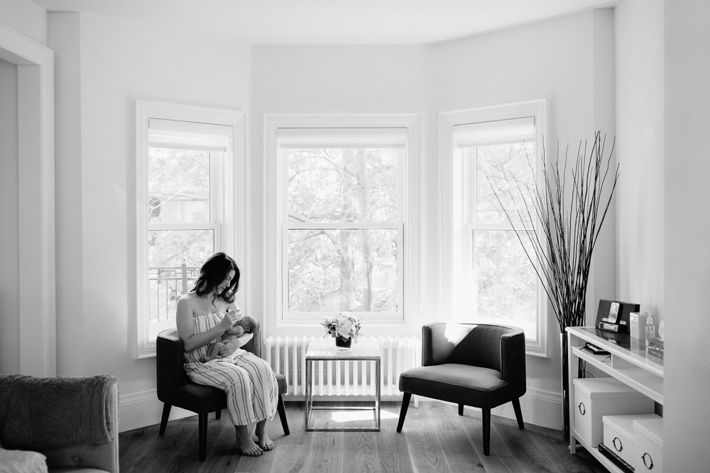 new mom with long dark hair sitting in chair in white, light filled room in front of window bottle feeding 2 week old baby boy in diaper - Newmarket Lifestyle Photography