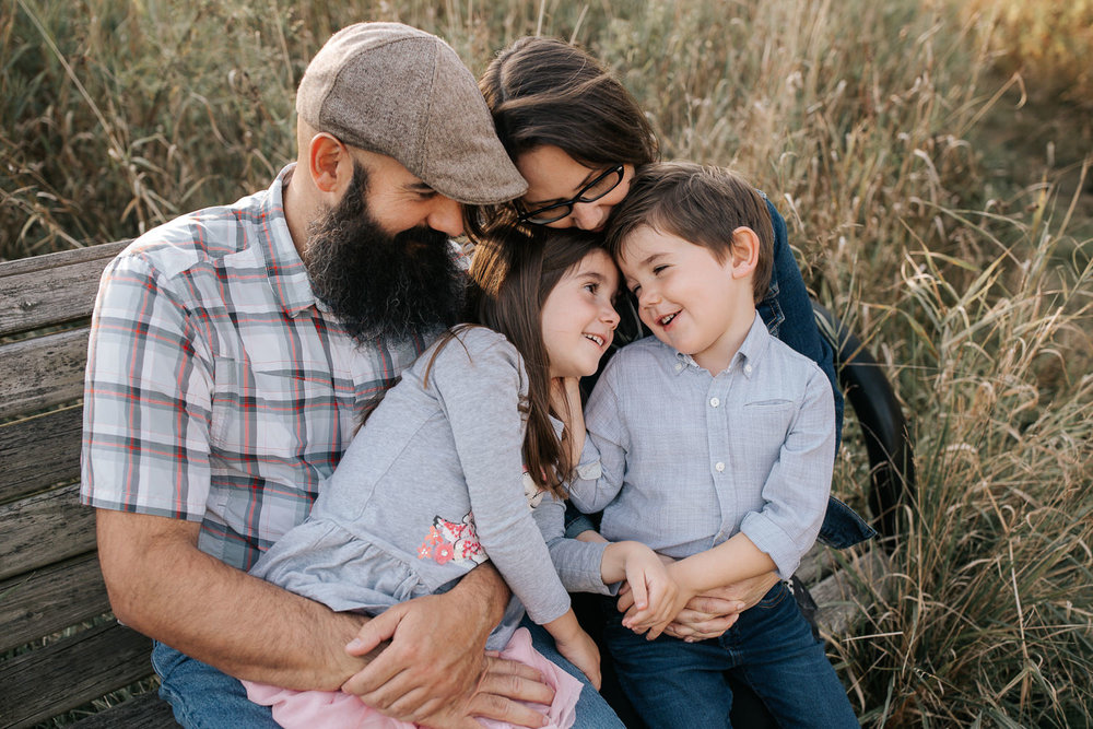 family of 4 sitting on park bench surrounded by tall grasses, 5 year old girl sitting on dad's lap, boy in mom's, snuggling, brother looking at sister - Stouffville Lifestyle Photography