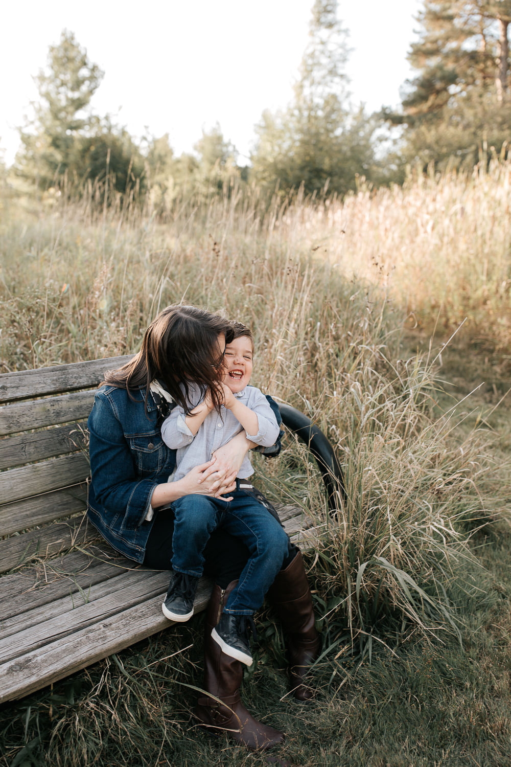 mother with dark brown hair sitting on park bench surrounded by tall grasses with 4 year old boy sitting in her lap, laughing as mom kisses son's face - York Region Lifestyle Photography