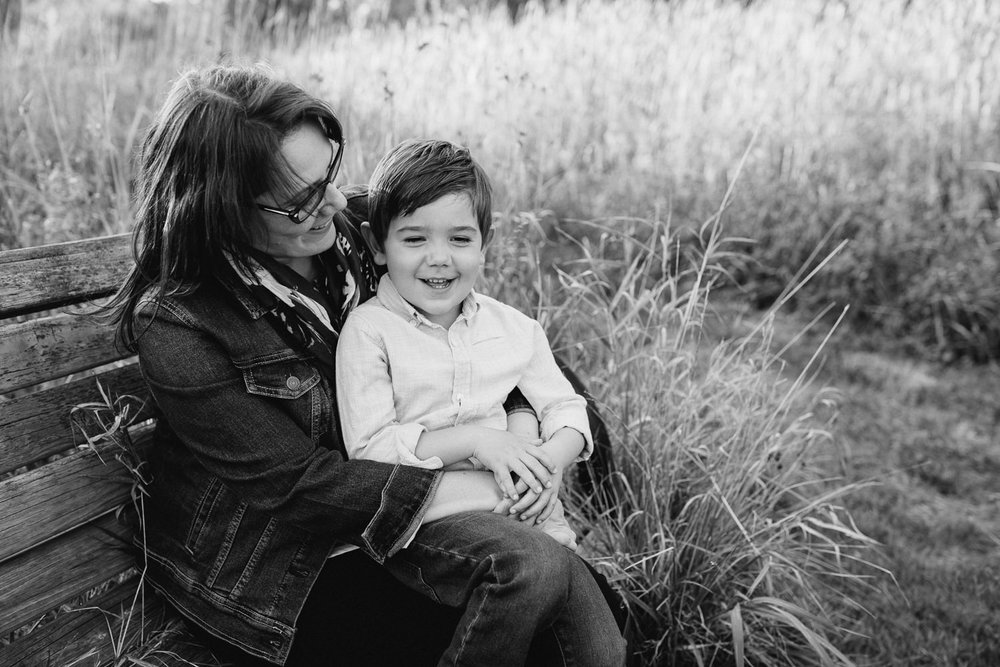 mother with dark brown hair sitting on park bench surrounded by tall grasses with 4 year old boy sitting in her lap, mom smiling at son as he smiles - Newmarket In-Home Photography