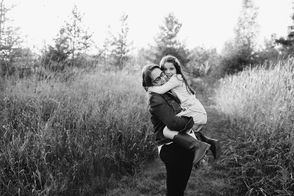 mother with dark brown hair standing in field surrounded by tall grasses with 5 year old girl in her arms, daughter hugging mom and looking at camera - York Region In-Home Photography