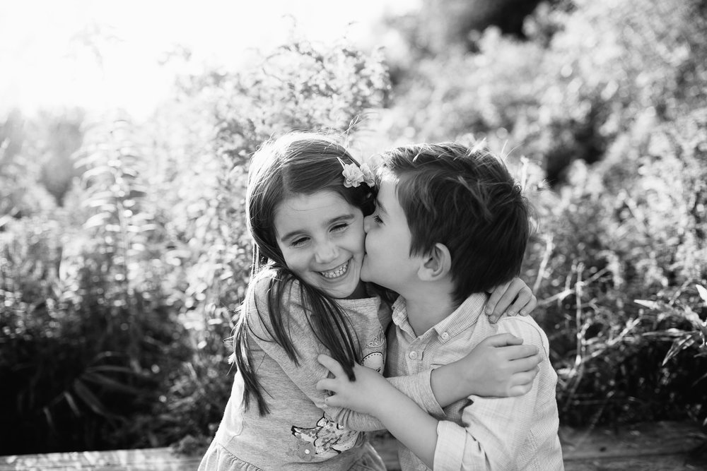 5 year old girl and 4 year old boy with dark hair sit on bench, sister hugging brother and smiling as he kisses her on cheek - Newmarket In-Home Photos